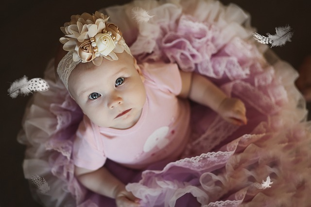 batole v růžové sukni a s květinovou ozdobou na hlavě